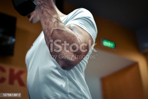 istock Muscular bodybuilder guy doing exercises 1075613912