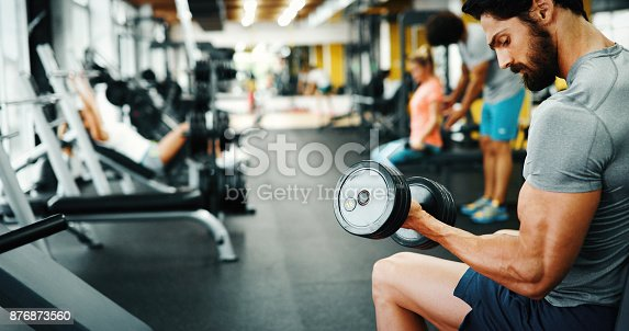 istock Muscular bodybuilder guy doing exercises 876873560