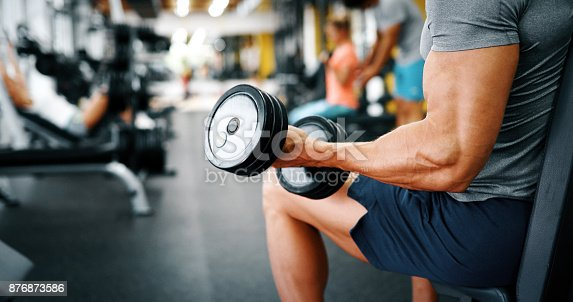 istock Muscular bodybuilder guy doing exercises 876873586