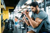 istock Muscular bodybuilder guy doing exercises 908985656