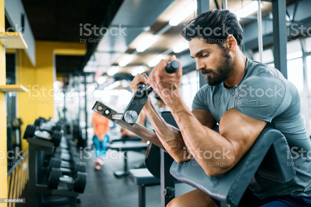 Muscular bodybuilder guy doing exercises stock photo