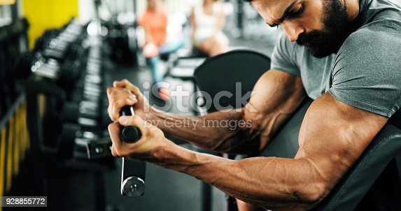 istock Muscular bodybuilder guy doing exercises 928855772