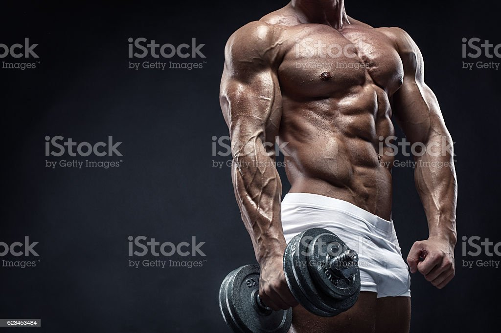 Muscular bodybuilder guy doing exercises with dumbbell stock photo
