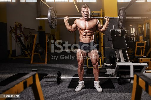 istock Muscular bodybuilder guy doing exercises with dumbbell 628094778