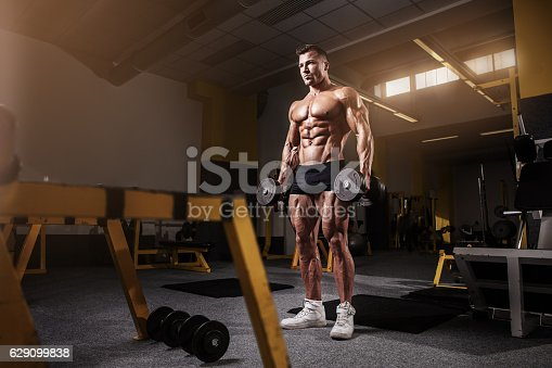 istock Muscular bodybuilder guy doing exercises with dumbbell 629099838