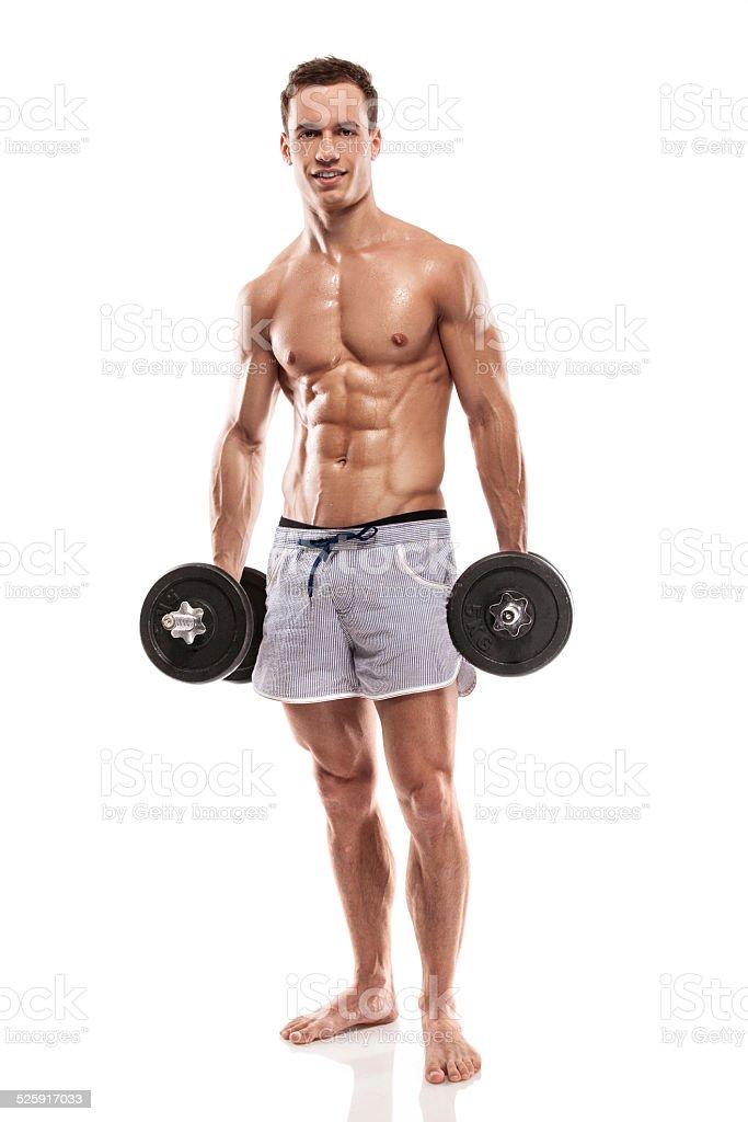 Muscular bodybuilder guy doing exercises with dumbbells stock photo