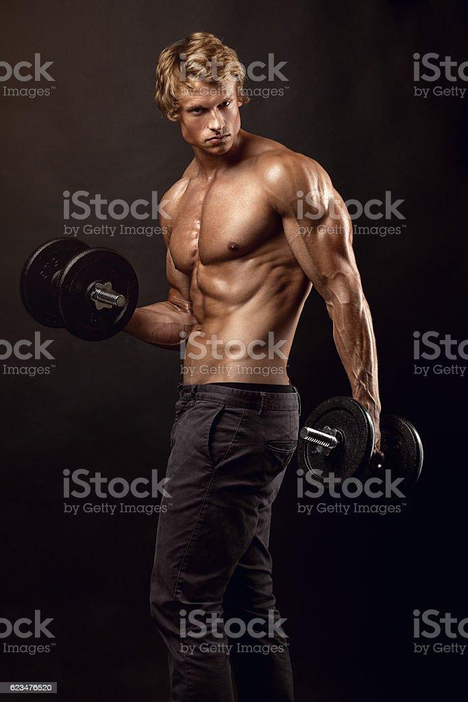 Muscoloso bodybuilder guy facendo esercizi con manubri  - foto stock