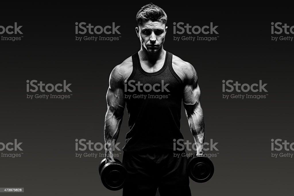 muscular bodybuilder guy  monochrome over grey background stock photo