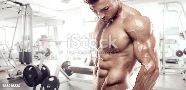 istock Muscular bodybuilder guy standing on gym 638516330