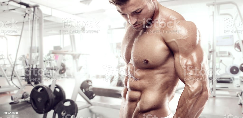 Muscular bodybuilder guy standing on gym stock photo
