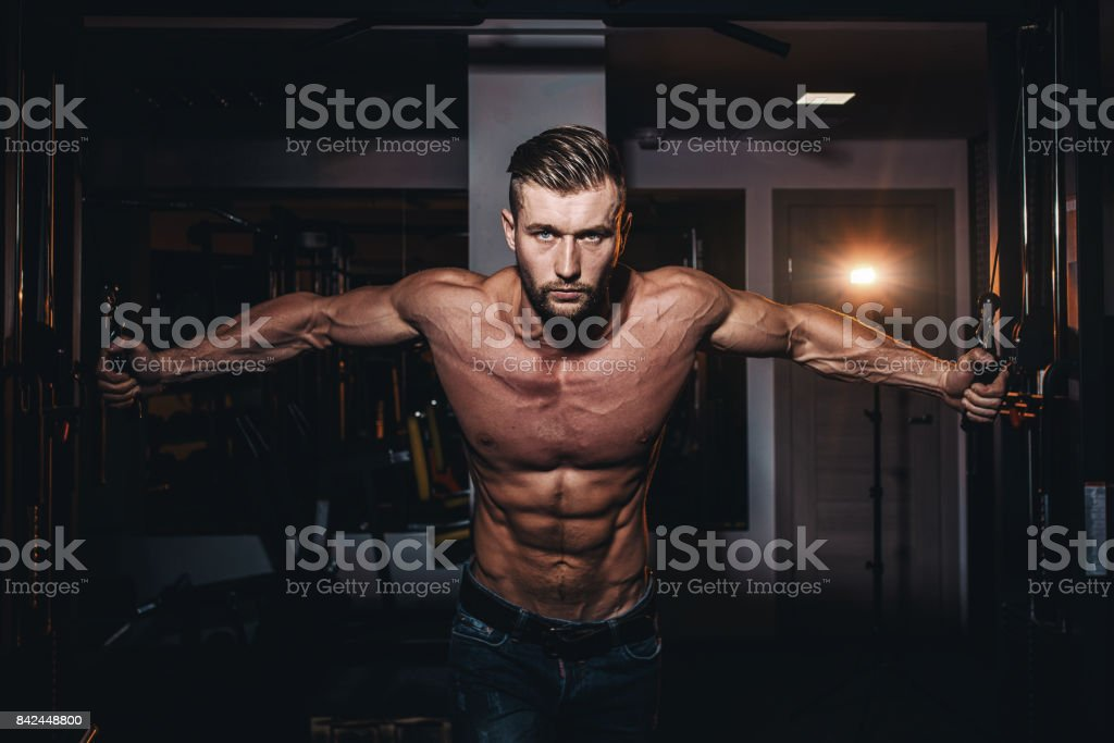 Muscular bodybuilder handsome men doing exercises in gym with naked torso. Strong athletic guy with abdominal muscles and biceps. stock photo