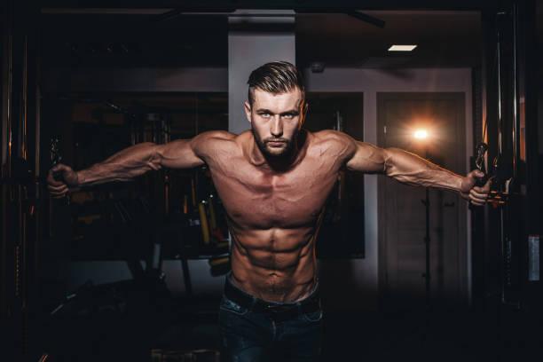 muskulöser bodybuilder gutaussehende männer machen übungen im fitness-studio mit nackten oberkörper. starke sportliche kerl mit bauchmuskeln und bizeps. - sexsymbol stock-fotos und bilder