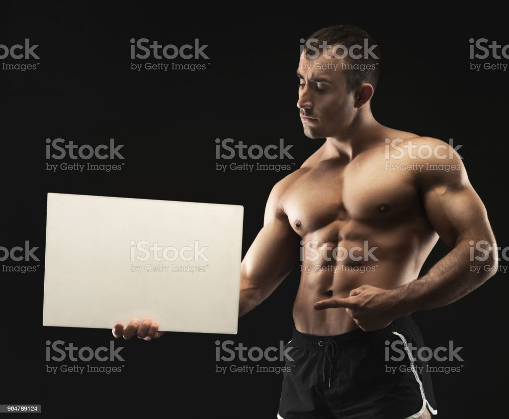 Muscular bodybuilder holding white blank banner at black background royalty-free stock photo