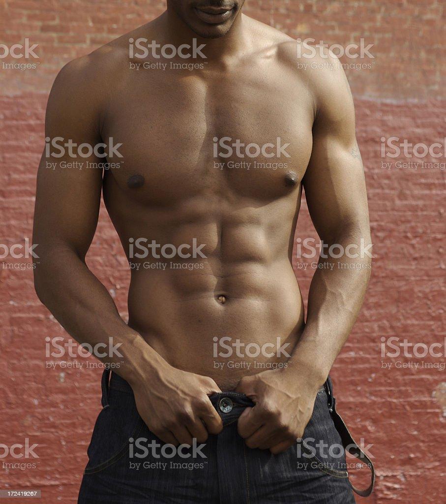 Muscular Brown Torso Shirtless Against Brick Wall stock photo