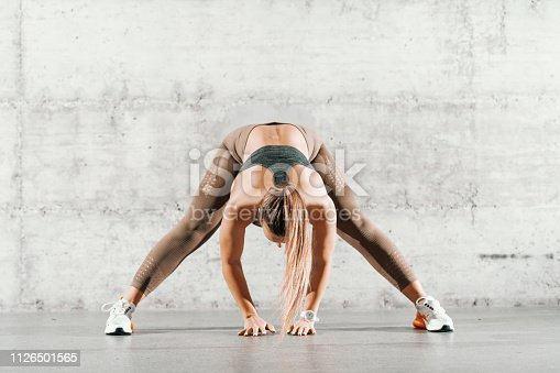 Muscular brunette with ponytail and in sportswear doing stretching exercise with legs spread out in front of brick wall.