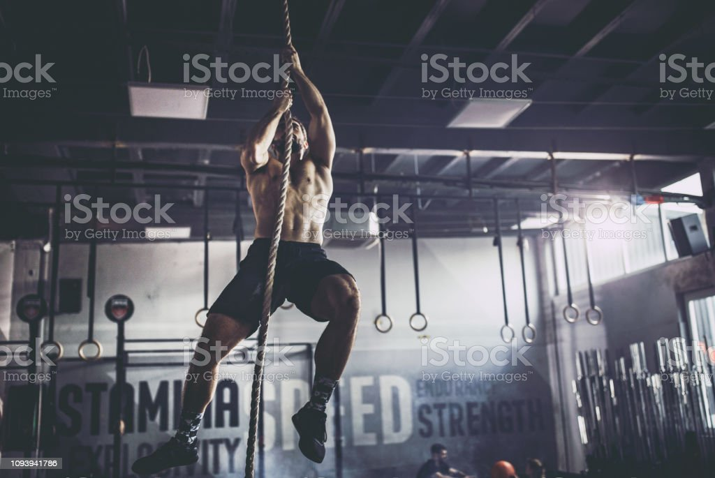 Muscular build athlete climbing up the rope in a gym.
