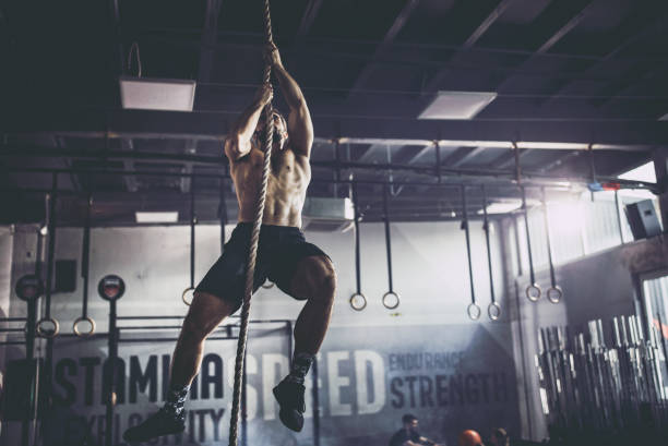 Muscular build athlete climbing up the rope in a gym. stock photo