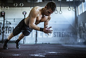 istock Muscular build athlete having gym training in a gym. 1223133311