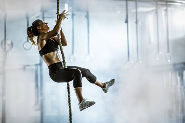 Muscular build athletic woman moving up the rope in a gym. stock photo