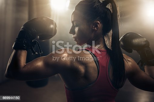 497607484 istock photo Muscular build female boxer showing her muscles in a health club. 669944150