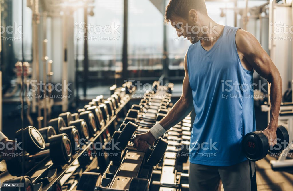 Muscular build sportsman taking weights from a rack in a gym. stock photo
