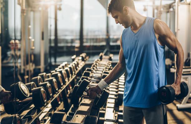 Construção muscular desportista levar pesos de um rack em um ginásio. - foto de acervo