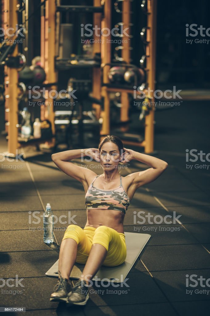 Muscular build woman doing sit-ups in a health club. royalty-free stock photo