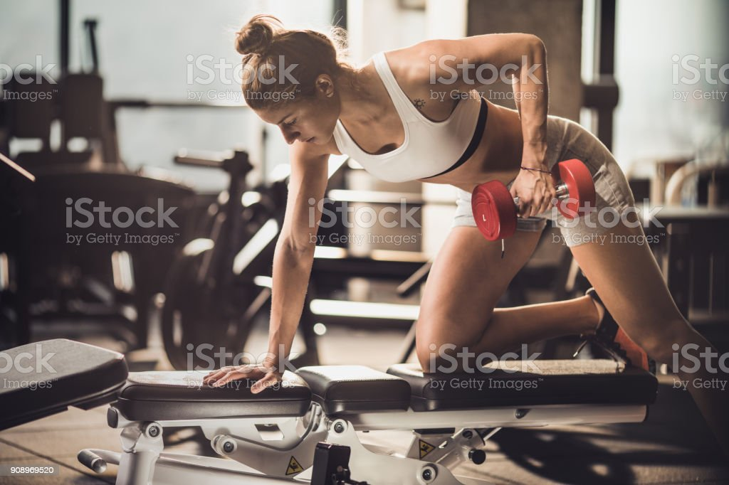 Muskulös Frau mit Hanteln im Fitnessstudio trainieren. – Foto