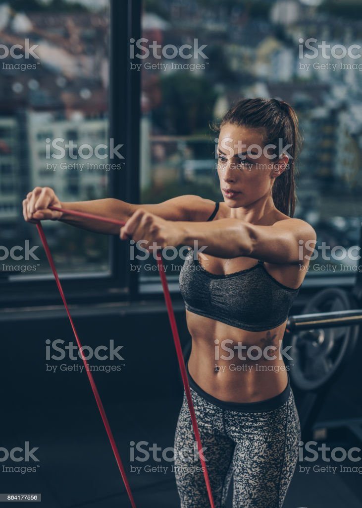 Muscular build woman exercising with elastic rope in a health club. royalty-free stock photo