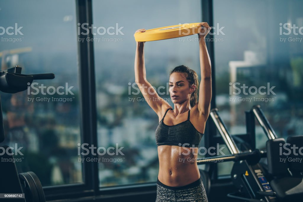 Muscular build woman having cross training in a gym while exercising with weight disk. stock photo