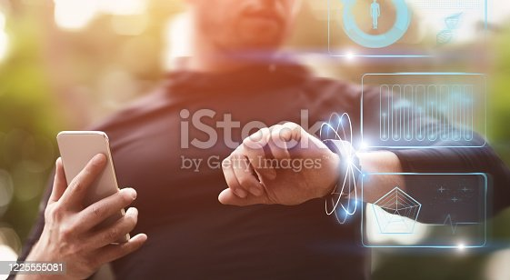 Modern Technology Concept. Guy holding smart phone checking wristband outdoors, panorama, HUD futuristic elements interface