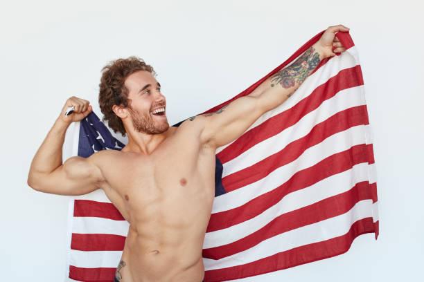 muskulöser fröhlichen mann posiert mit flagge - rebellenflaggen tattoos stock-fotos und bilder