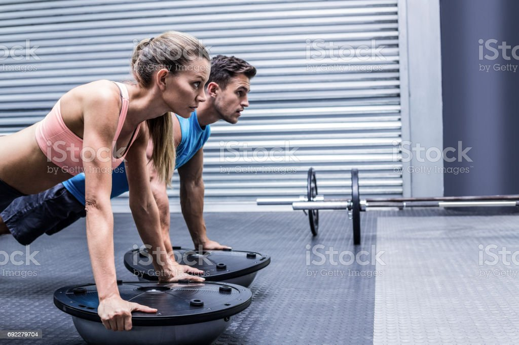 Muscular couple doing bosu ball exercises stock photo