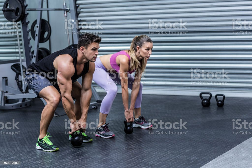 A muscular couple lifting kettlebells stock photo