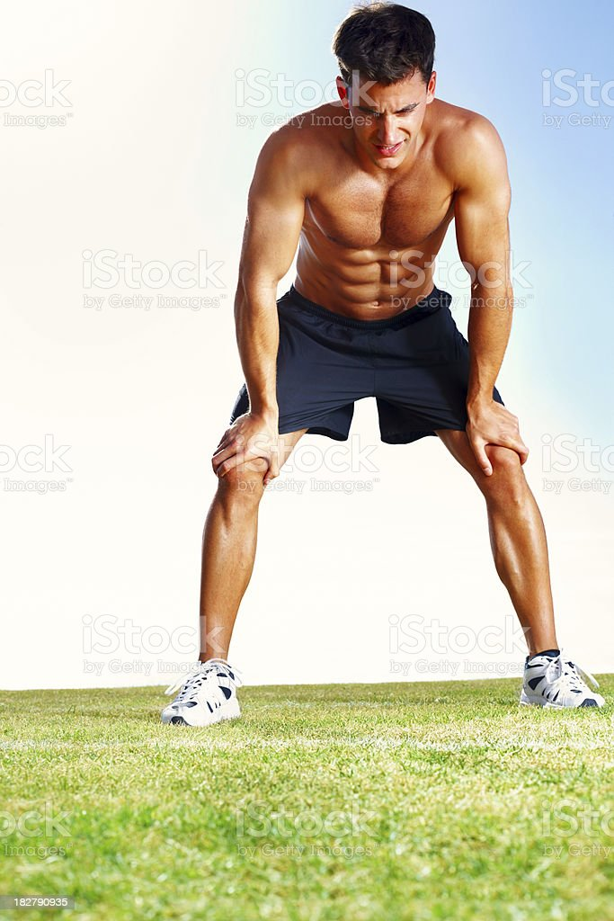 Muscular exhausted young guy after a jog on field royalty-free stock photo