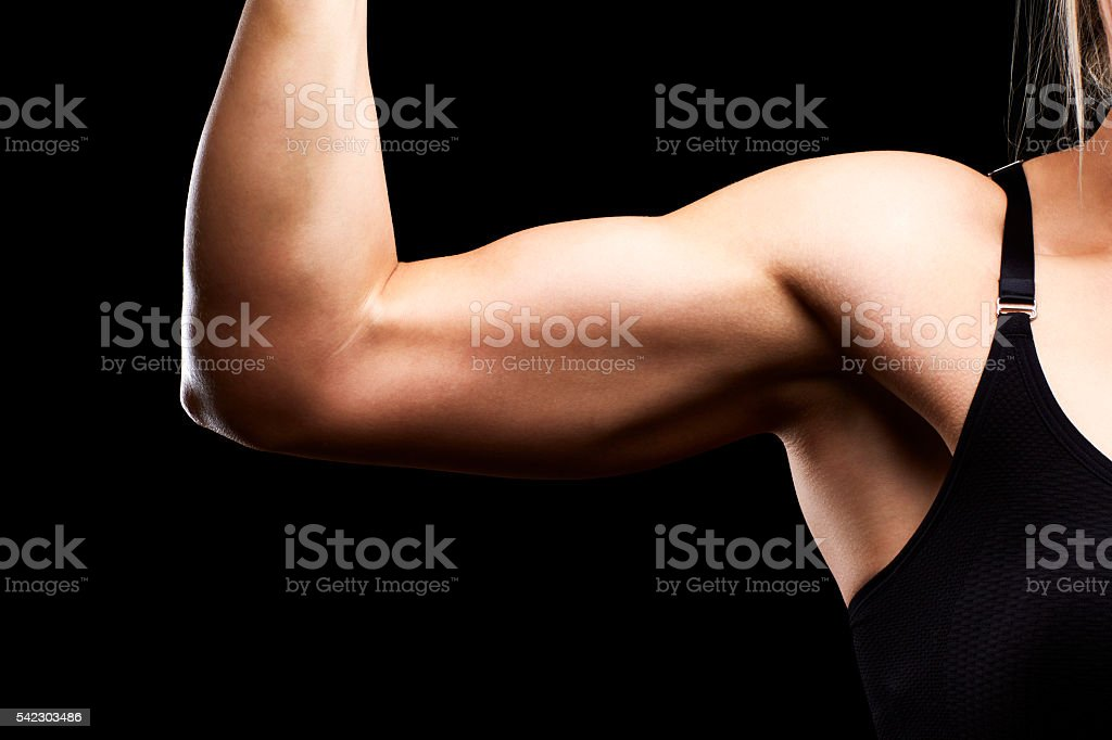 Muscular female athlete flexing bicep muscle stock photo