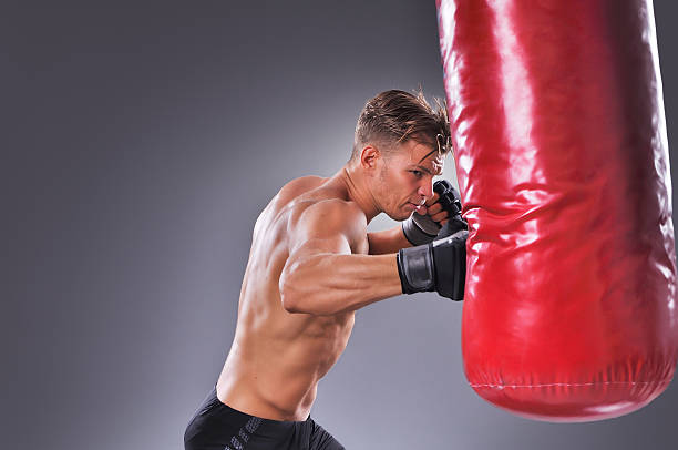 muscular fighter practicing some kicks with punching bag - six pack trainer stock-fotos und bilder