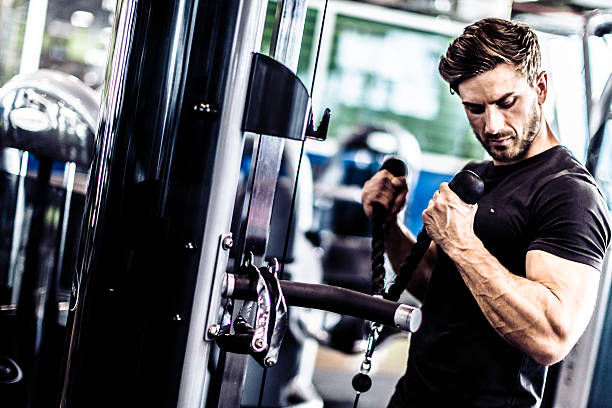 Muscular Fit Man Exercising in a Gym A fit young man Exercising in a Gym. exercise machine stock pictures, royalty-free photos & images