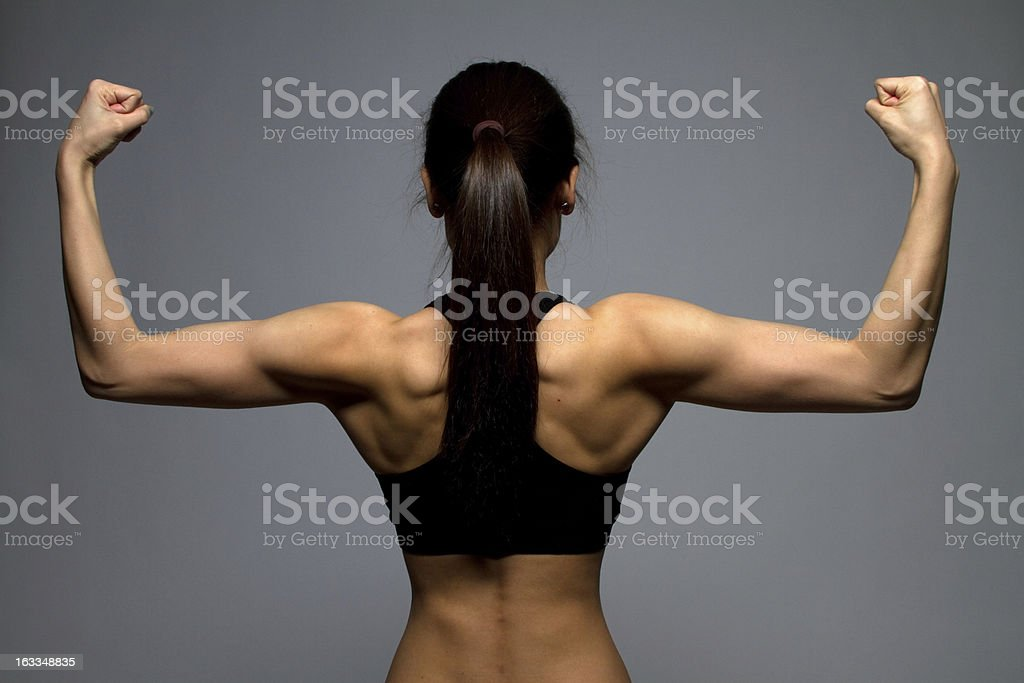 Muscular girl flexing stock photo