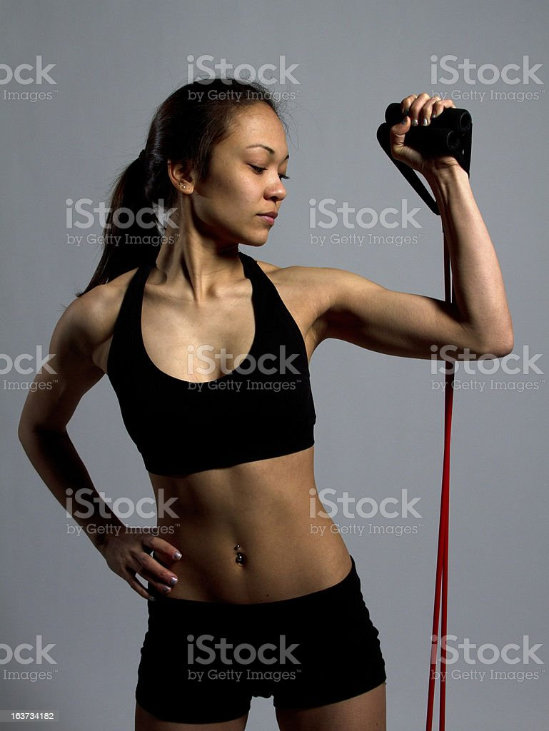 Muscular girl flexing with resistance cord royalty-free stock photo