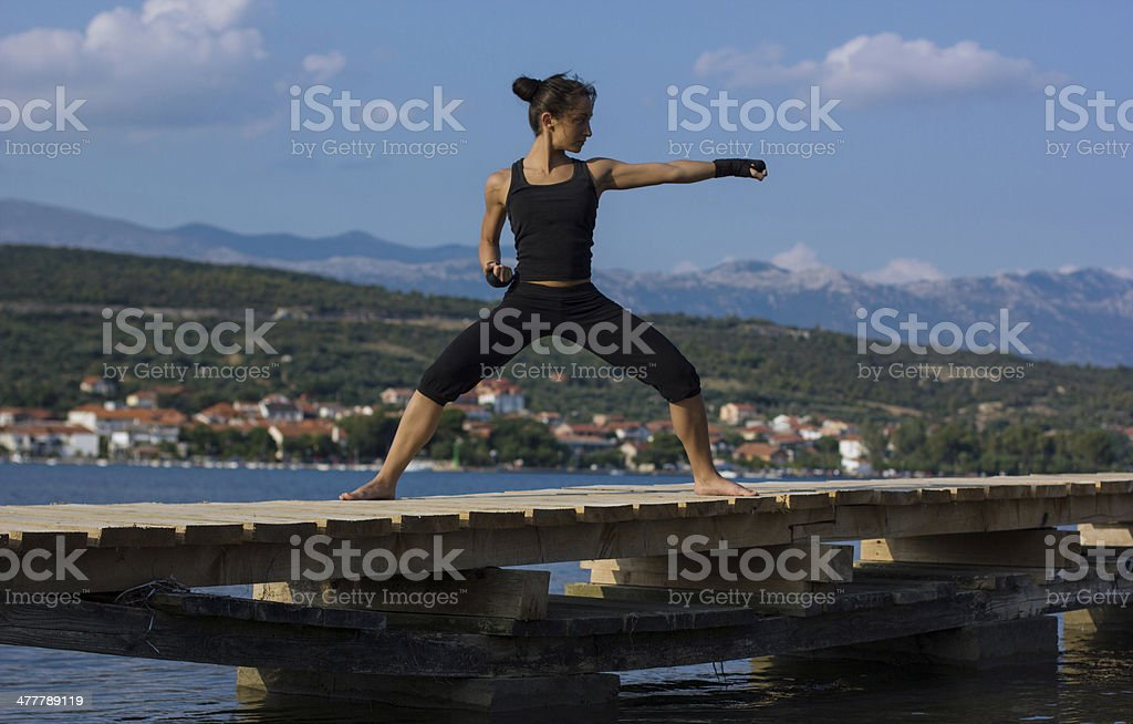 Muscular girl working out on the wooden bridge stock photo