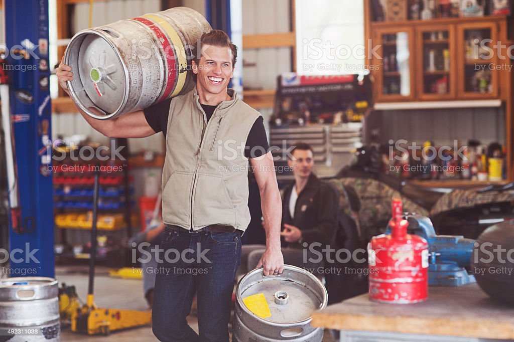 Muscular Guy Carrying Two Kegs of Beer to the Garage stock photo