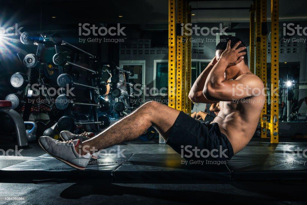 Chico musculoso haciendo sit ups en el gimnasio con los demás en segundo plano. Atleta joven haciendo ejercicios de estómago en el gimnasio moderno. Ajuste guapo haciendo abdominales en el gimnasio. foto de stock libre de derechos
