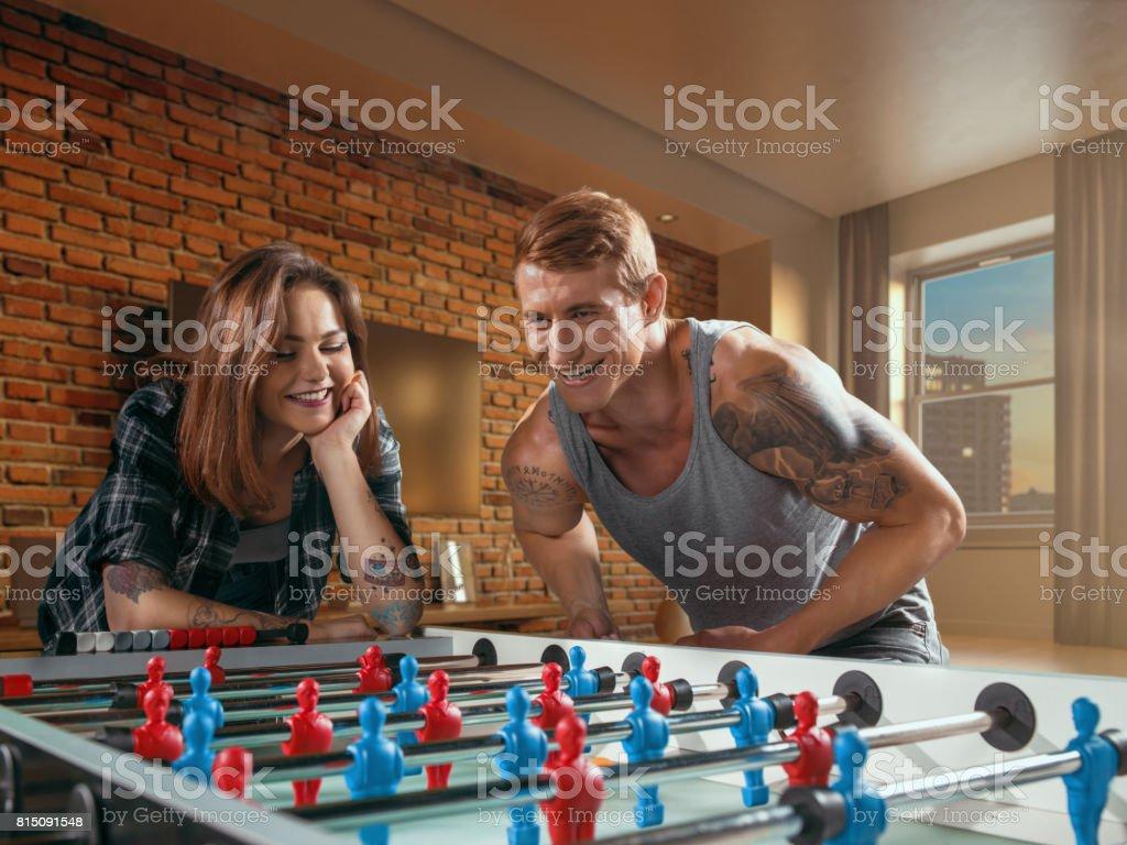 Um cara musculoso joga o jogo de futebol/chutador de mesa - foto de acervo