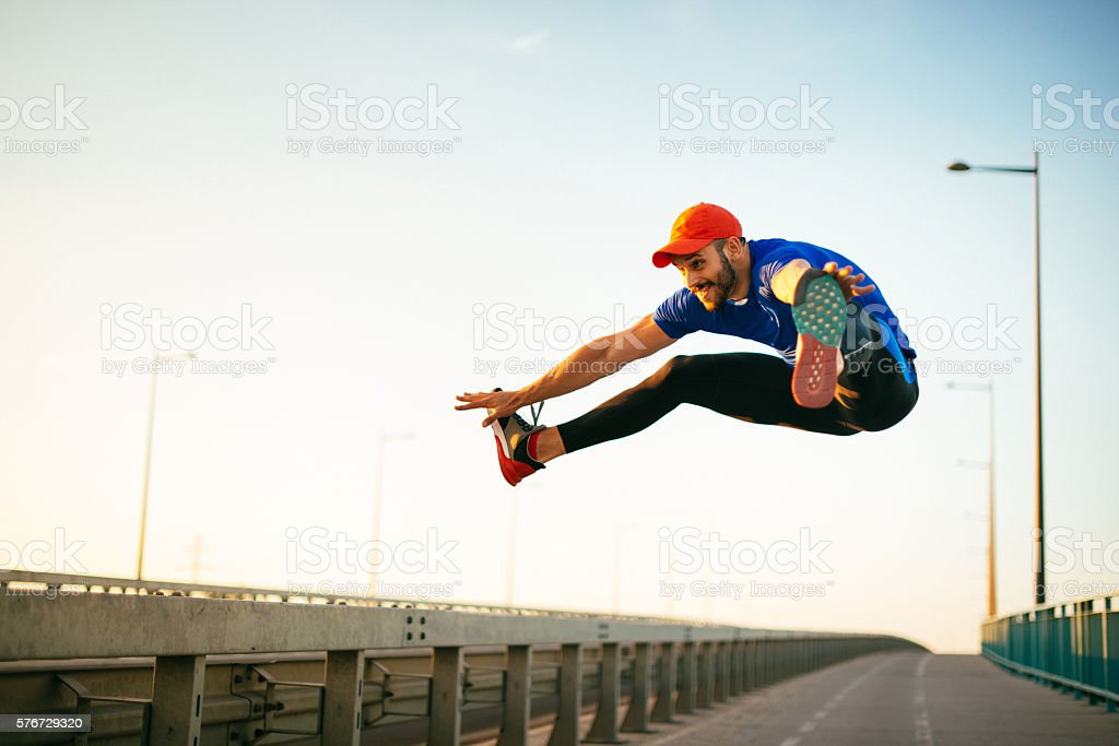 Muscular gymnast jumping with legs split in mid-air stock photo