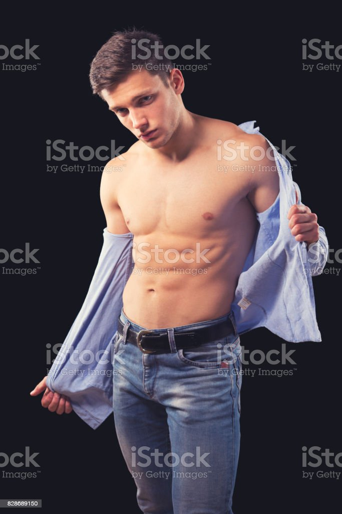 Muscular handsome young man taking off his shirt stock photo
