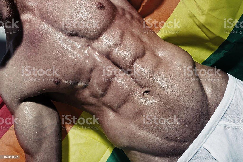 Muscular hunk holding Gay rainbow flag royalty-free stock photo
