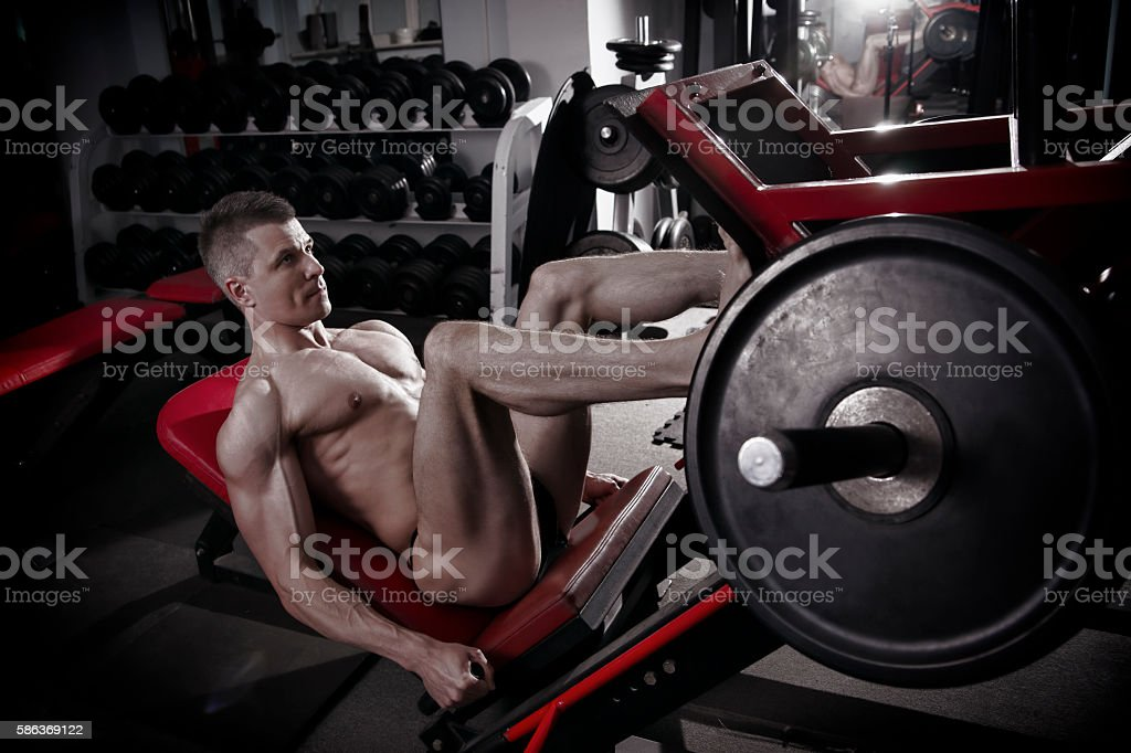 Muscular legs. Handsome bodybuilder workout on trainer in the gym stock photo