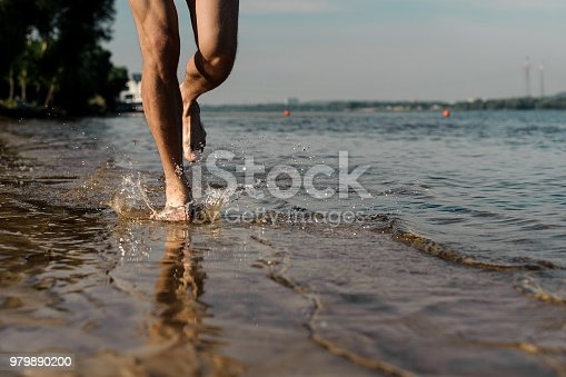 174919648 istock photo Muscular male feet running along the beautiful river bank 979890200