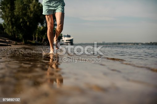 174919648 istock photo Muscular male feet running along the river bank 979890132
